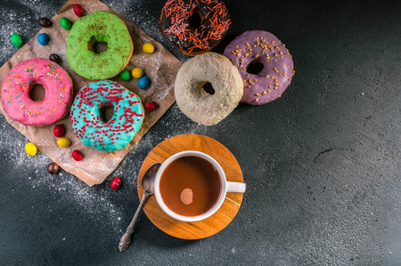 Donuts with colorful icing and hot cocoa on a dark background. Top view