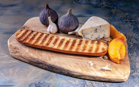 Ripe figs, noble cheese with mold, peach slices and baguette on a cutting board.