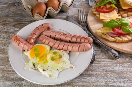 Fried eggs, sausages, sandwiches with cheese, tomato and basil