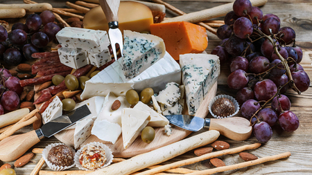 Different sorts of cheese and grapes on a wooden background. Close-Up