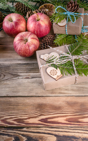 Christmas background. Christmas gifts, red apples, fir branches and cones on a wooden background. Vertical shot