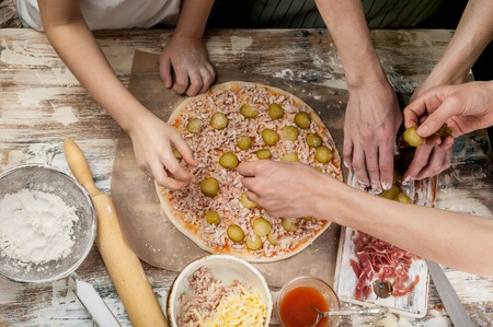 Cooking pizza with mom. Mom and her children make delicious pizza with prosciutto and cherry tomatoes. Food concept. Top view Фото со стока