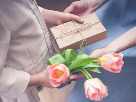 Happy Mother's Day. Little girl congratulates mom and gives a gift and flowers tulips. Toning. Selective focus