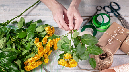 Florist at work. Female hands collect a wedding bouquet of roses. People in the process of work Banco de Imagens