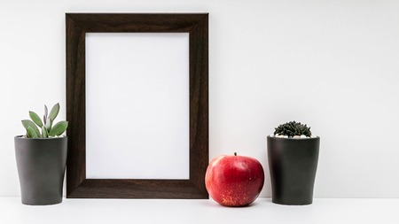 Empty dark photo frame, two succulents in dark pots and a red juicy apple on a white background. Scandinavian style in the interior.