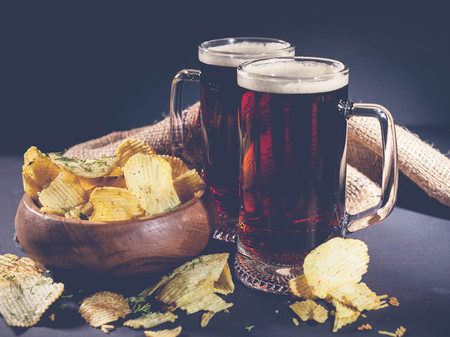 Red craft beer and potato chips in a wooden bowl on a dark background. Low key lighting.