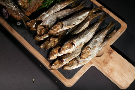Hot smoked sprat, red onion and dill on a cutting board on a dark background. Archivio Fotografico
