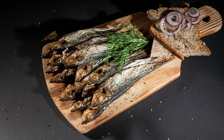 Hot smoked herring, red onion and dill, rye bread on a cutting board on a dark background.