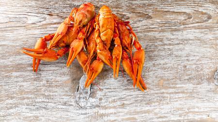 A tasty boiled crayfish on wood background