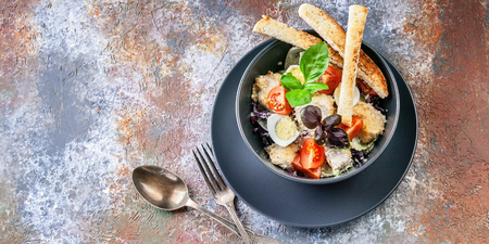Caesar salad with chicken, cherry tomatoes, croutons and basil in a dark blue bowl on a rusty background. Top view