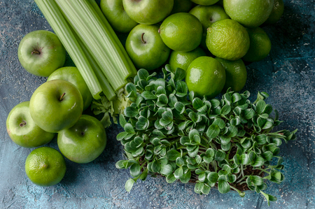 Top view green apples, celery, limes and milk thistle microgreen on a concrete background. Detox program, diet plan, weight loss.
