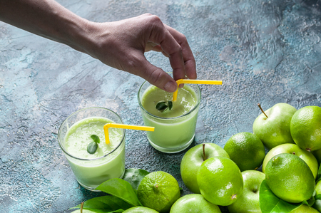 Female hand and smoothies apples and limes on a dark blue concrete background. Detox programm Stock Photo