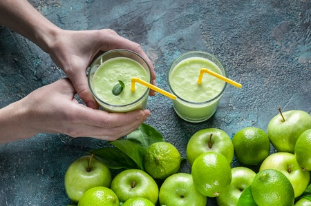Female hands hold smoothies apples and limes on a dark blue concrete background. Detox programm Stock Photo