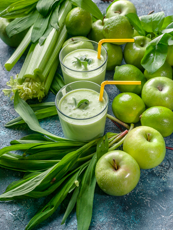 Detox program. Smoothie green apples, celery, ramson and limes on a concrete background.