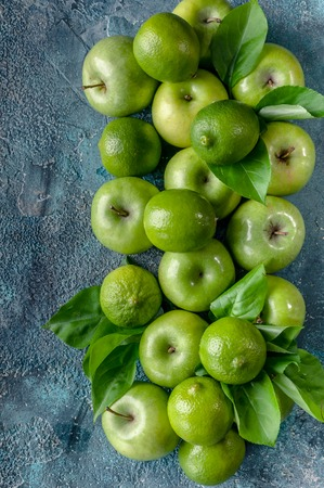 Apples and limes on a dark blue concrete background. Top view. Vertical shot