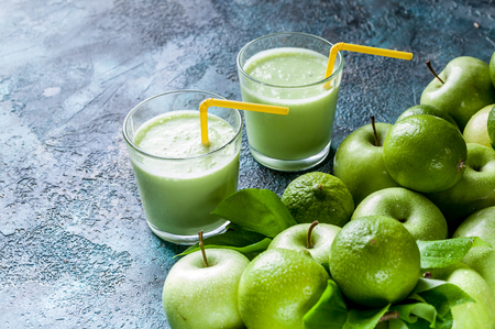Smoothies apples and limes on a dark blue concrete background. Detox programm Stock Photo
