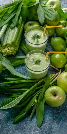 Vertical food banner detox program. Smoothie green apples, celery, ramson and limes on a concrete background. Stock Photo