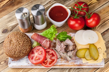 Meat, cheese, tomatoes, onions, cucumbers, lettuce, sauce, spices and bacon. Hamburger ingredients.