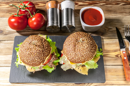 Big homemade sandwich or hamburger with tomatoes, cheese, meat and salad on a wooden table. Stock Photo