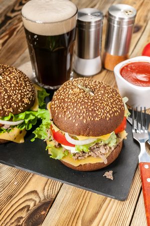 Big homemade hamburger with beef, tomatoes, cheese, meat and salad on a wooden table. Dark beer, sauce and spices. Vertical shot