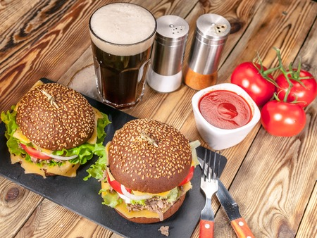 Big homemade hamburgers with beef, tomatoes, cheese, meat and salad on a wooden table. Dark beer, sauce and spices.