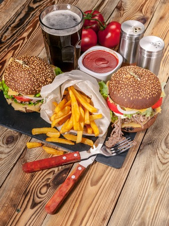 Big homemade hamburgers, french fries and dark beer. Hamburgers with beef, tomatoes, cheese, meat and salad on a wooden table.