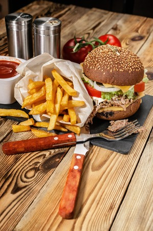 Large homemade hamburgers and french fries. Hamburgers with beef, tomatoes, cheese, meat and salad on a wooden table.