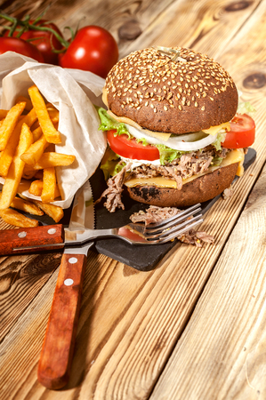 Close-up big homemade hamburgers, french fries and dark beer. Hamburgers with beef, tomatoes, cheese, meat and salad on a wooden table. Stock Photo