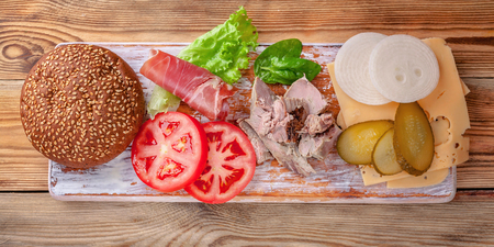 Hamburger ingredients. Meat, cheese, tomatoes, onions, cucumbers, lettuce and bacon. Food banner Stock Photo
