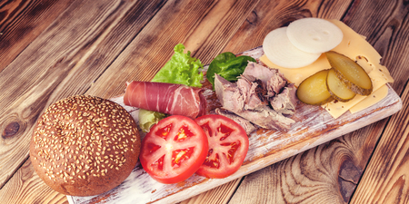 Food banner Hamburger ingredients. Meat, cheese, tomatoes, onions, cucumbers, lettuce and bacon.