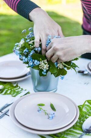 Hands florist-decorator make a bouquet of forget-me-not flowers and fern leaves. Decoration of a white rustic table. White dishes Stock Photo