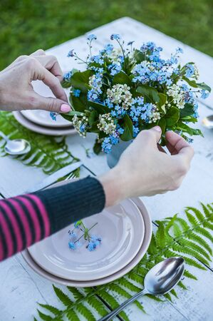 Top view florist makes a bouquet of forget-me-not flowers and fern leaves. Decoration of a white rustic table. White dishes