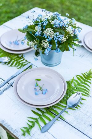 Close-up elegant bouquet of flowers on blue forget-me-not a white rustic table. Outdoor white table decoration. Vertical shot 스톡 콘텐츠