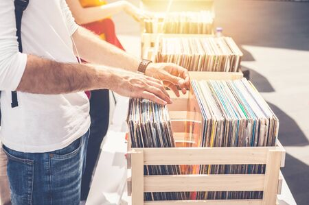 Man browsing vinyl album on sale. Beautiful male hands in the frame. Stock Photo