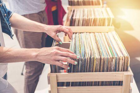 Woman choosing vinyl records on sale. Elegant womens hands in the frame.