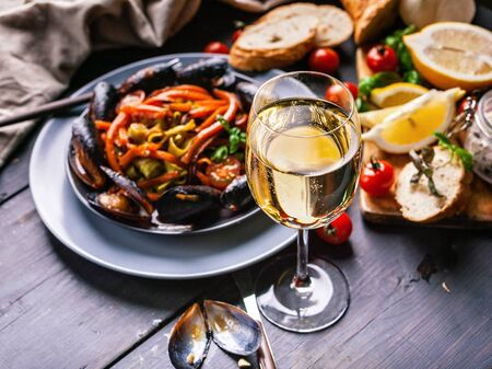 A glass of dry white wine on the background of Italian cuisine. Pasta, mussels and wine.