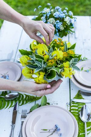 Florist making elegant bouquet of yellow irises on a white wooden table. Rustic style decoration