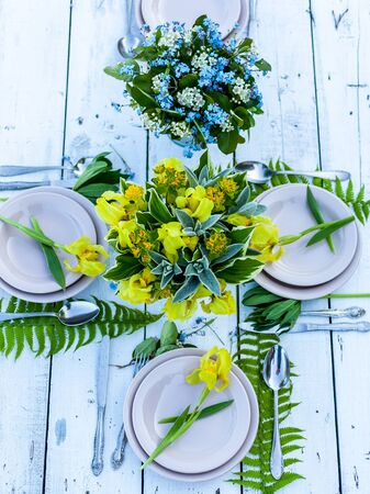 Wedding decoration in rustic style. Florist design. Bouquets of irises and forget-me-nots. Outdoor Wedding. Top view Stock Photo