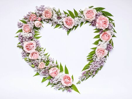 Wedding frame of flowers in heart-shaped: rose, lilac, rowan leaves on a white background. Floral pattern. Copy space for text