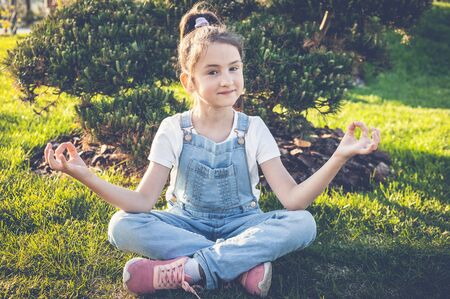 Young girl practice yoga and meditates in the lotus position in the Japanese garden. Calm and happy teenager Stock fotó