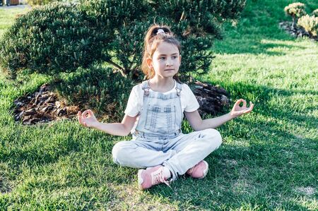 Sweet girl meditates in the Japanese garden. Calm and happy child Stock fotó