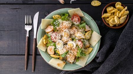 Food banner. Caesar salad with quail egg, fried chicken, parmesan cheese and croutons on a dark rustic background. Horizontal shot