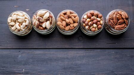 Different kinds of nuts in jars on a dark wooden background. Copy space