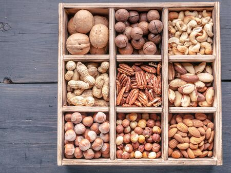 Wooden box with different kinds of nuts on a dark wooden background. Top view