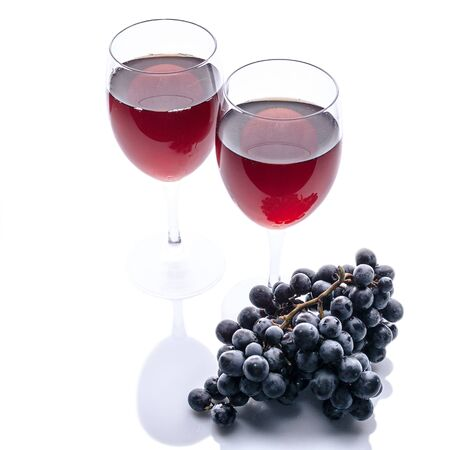Red wine in glasses and a bunch of black grapes on a white background. Isolated composition