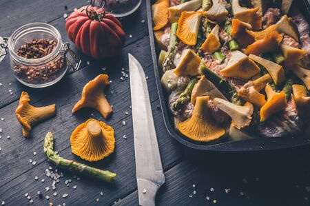 Fresh chanterelles and asparagus in a cast-iron baking dish on a dark wooden table.