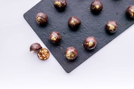 Top view handmade chocolates with peanuts and honey. Gourmet chocolates on a white background on the black ceramic board