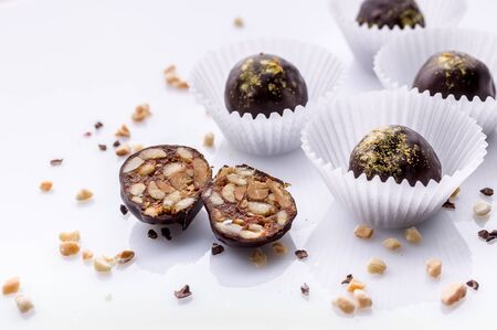 Handmade chocolates with peanuts and honey. Gourmet chocolates on a white background. Close-up. Soft focus