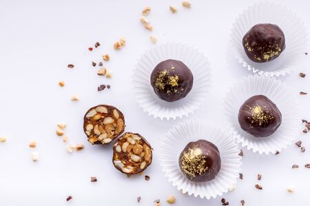 Top view handmade chocolates with peanuts and honey. Gourmet chocolates on a white background. Close-up. Soft focus