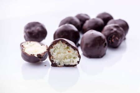 Handmade chocolates with coconut and honey. Gourmet chocolate on a white background. Close-up Reklamní fotografie
